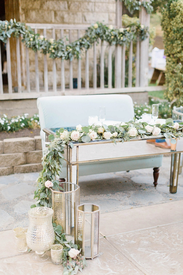 Sweetheart table with mirror table and floral garland