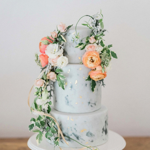 Gray painted wedding cake with gold leaf and fresh florals