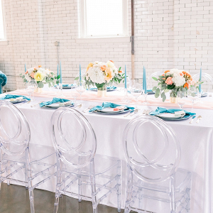 Coral and teal wedding table with clear chairs