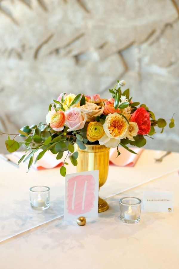 Yellow, orange, and pink centerpiece with a watercolor table number