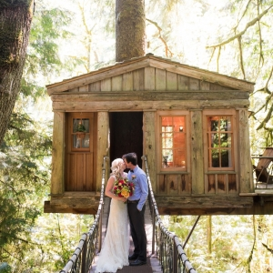 Bride And Groom In Front Of A Treehouse Venue
