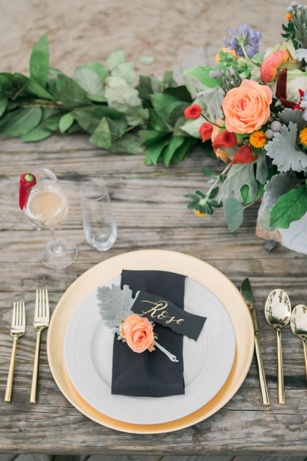 Gold rimmed plates and gold flatware with black and peach details