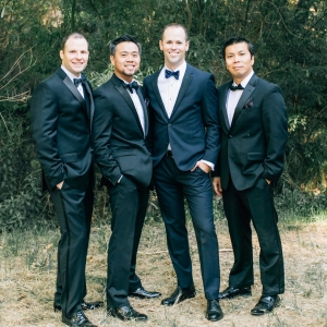 Groom in blue suit and groomsmen in black tuxedos