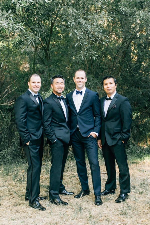 Groom in blue suit and groomsmen in black tuxedos