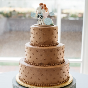 Gold wedding cake with bride, groom and dog topper