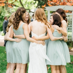 Bride with bridesmaids in mint dresses hugging