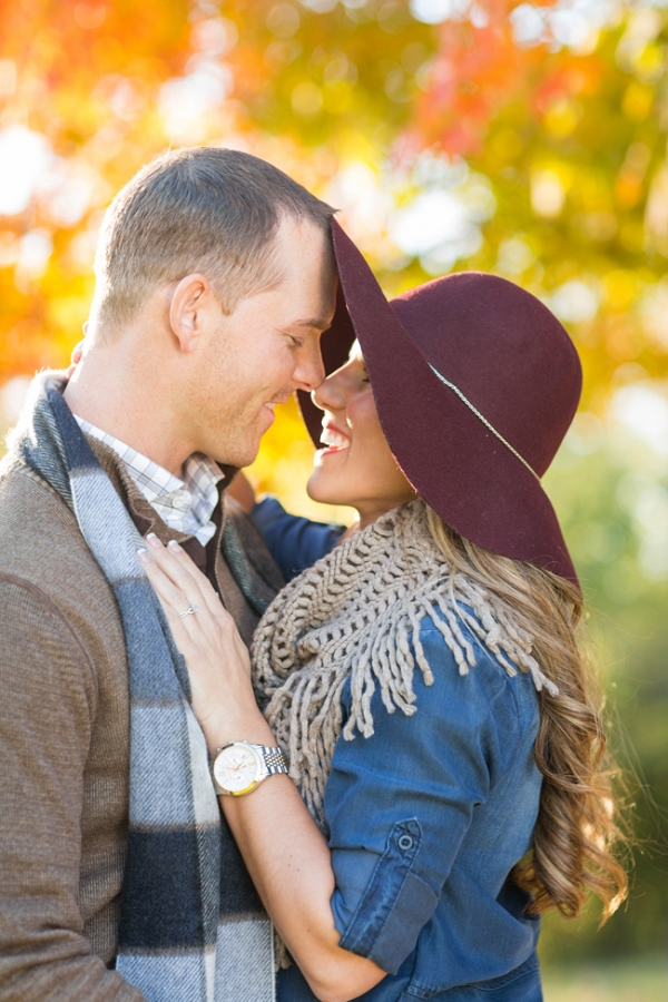 Engaged Couple with a Floppy Hat & Fall Colors Behind
