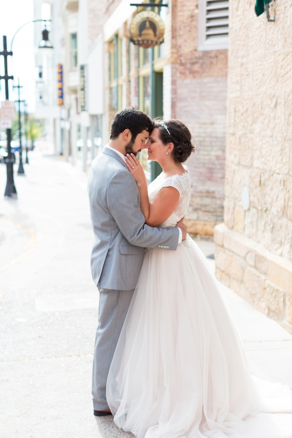 Groom In Gray And Bride In A Sleeveless Lace And Tulle Gown