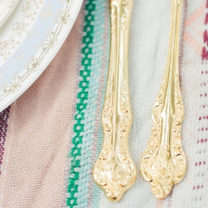 Gold flatware, striped table cloth, and a pale pattern china