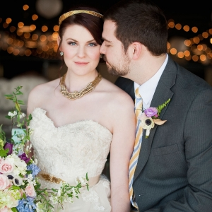 Bride with gold accessories and groom in gray suit