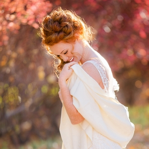 Bride In Front Of Fall Foliage With Sunlight Behind