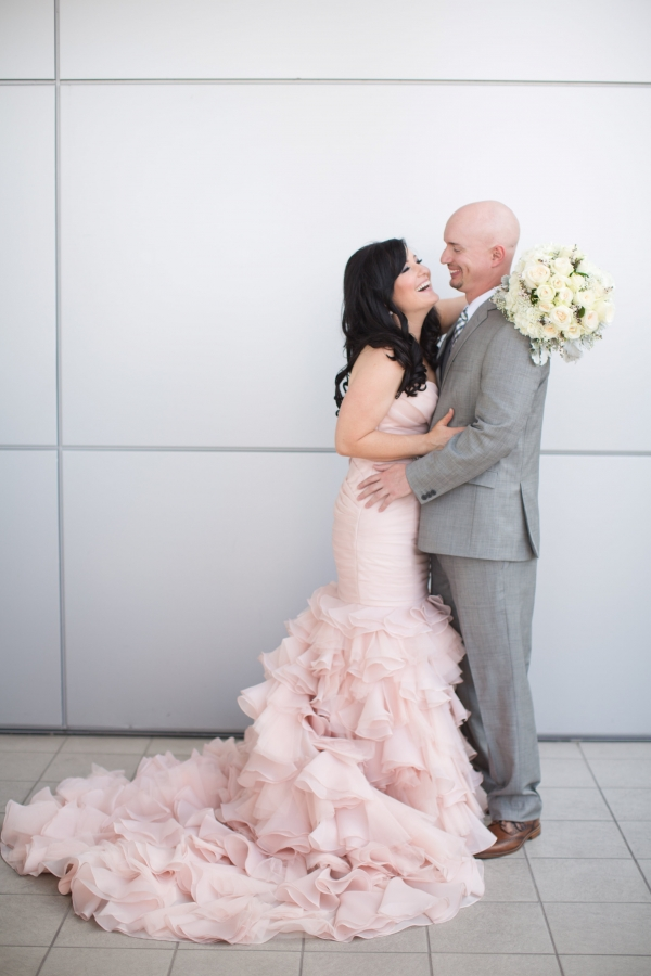 Bride in blush gown and groom in gray suit