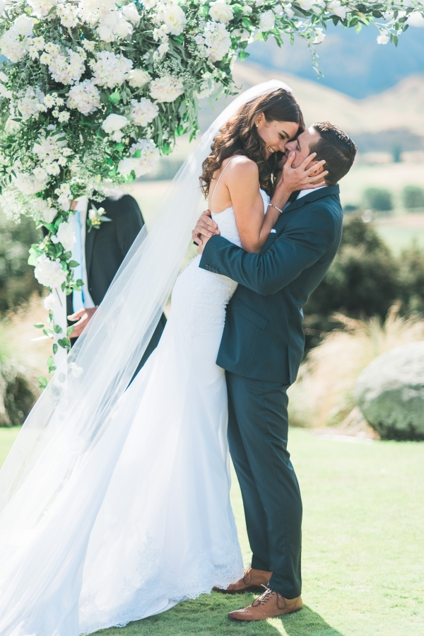 Bride and groom under white and green floral arch during ceremony