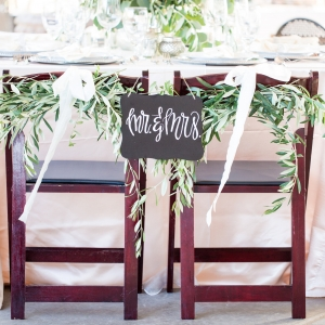 Mr. & Mrs. Chalkboard sign on wooden chairs