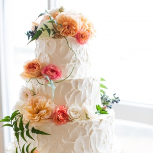 Buttercream cake with peach, orange and ivory flowers
