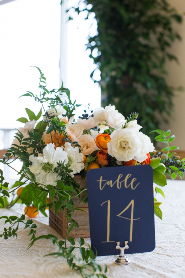 Elegant orange, white, and navy centerpiece and table number