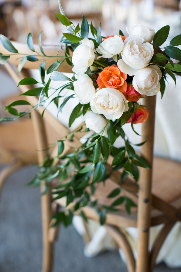 Elegant wooden chair with ranunculus, roses, and greenery