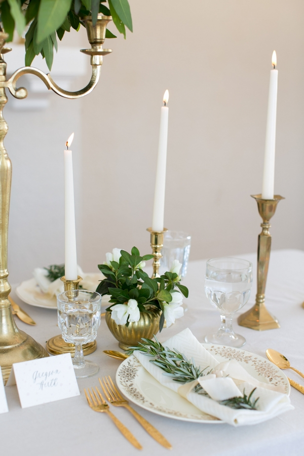 Gold candlesticks, gold flatware and gold decor plates