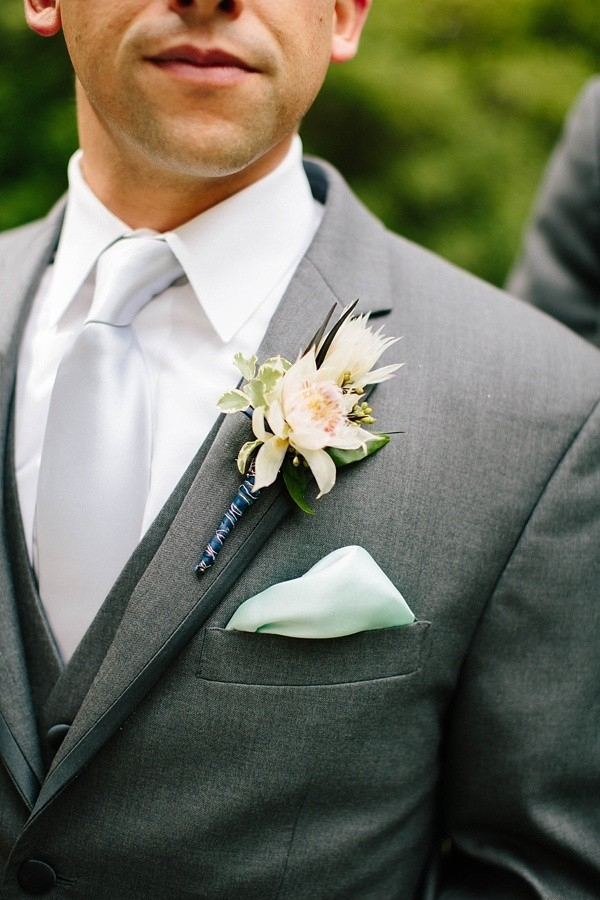 Groom boutonniere with blushing bride protea