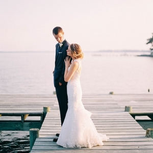 Bride and groom on a dock on the bay