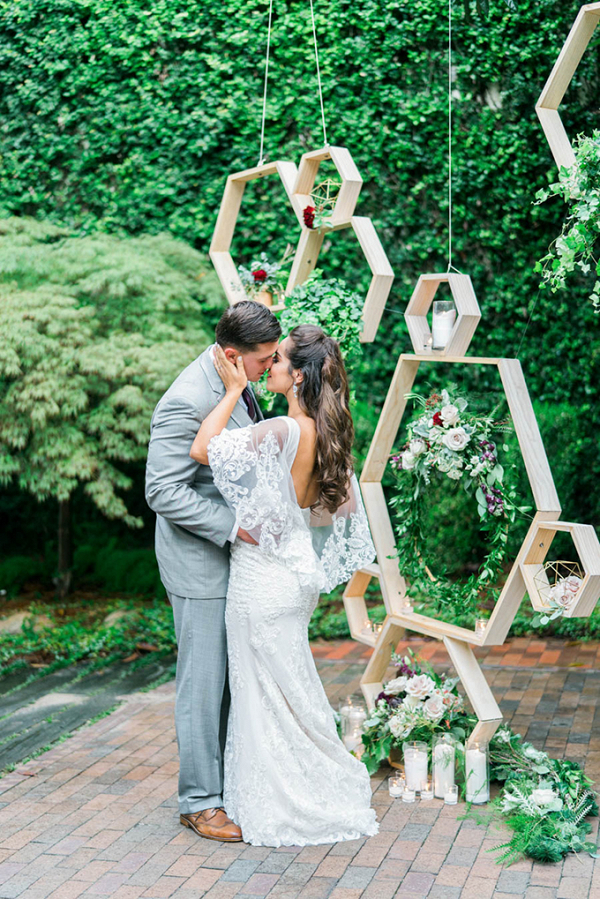 Couple in front of hanging honeycomb backdrop
