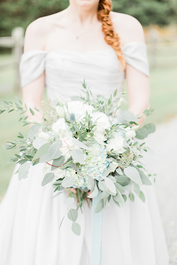 Bride in gray wedding dress with greenery bouquet