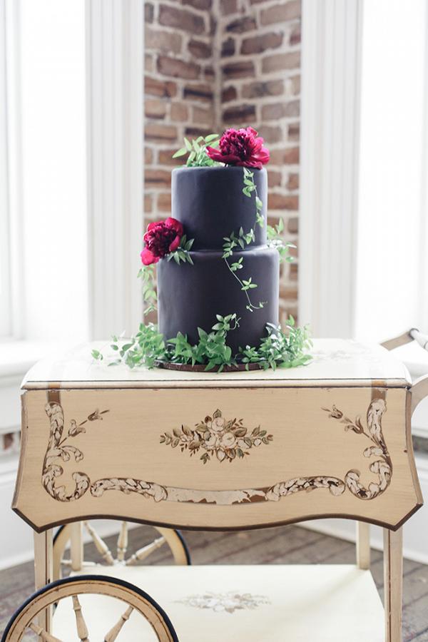 Black wedding cake with fresh florals