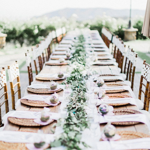 Long table wedding reception with terrarium place settings