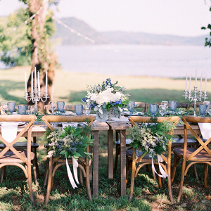 Long farm table lakeside wedding with blue and green florals