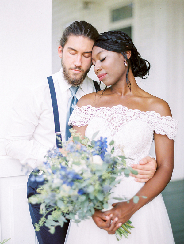 Bride in off white lace dress with blue bouquet