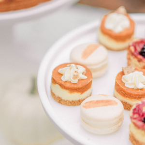 mini assorted cheesecakes on a white cake stand