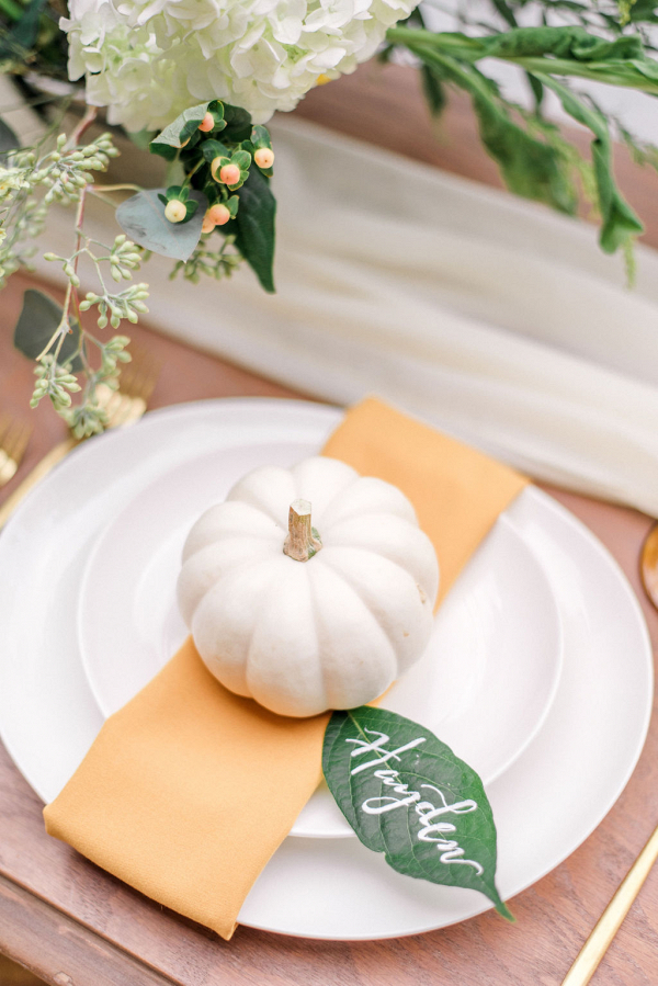 mini white pumpkin in a place setting with a hand written leaf place card holder
