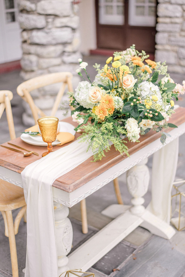 stunning tablescape with a white cheesecloth and mustard colored goblets and florals
