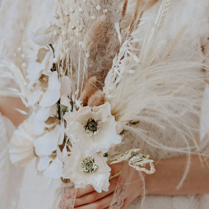 bride holding a white orchid bouquet