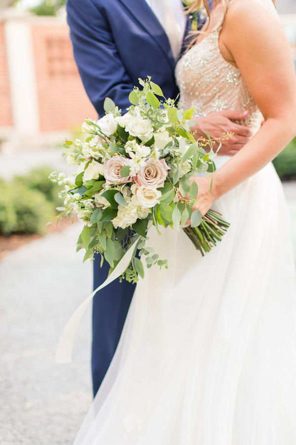 bride holding a white and blush rose bouquet