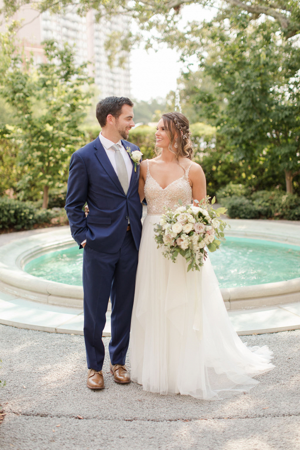 bride and groom in front of a fountain