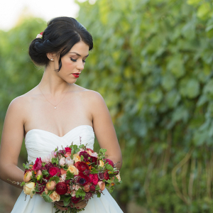Beautiful bride in a simple white gown in a vineyard
