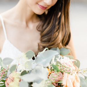 Bride looking down and holding a rose bouquet