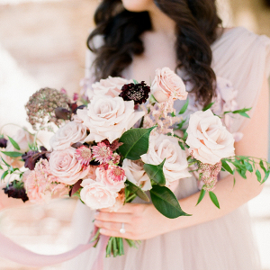 Bride with beautiful long brown hair holding a mauve bouquet