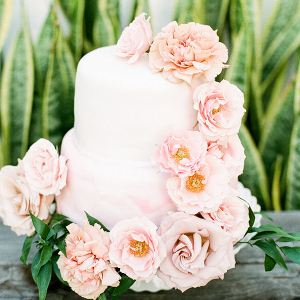 White two tier cake with pink cascading roses