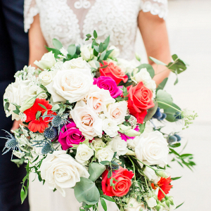 bride holding a pink orange and white bouquet