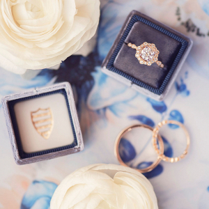 navy blue ring box with a gold halo diamond ring