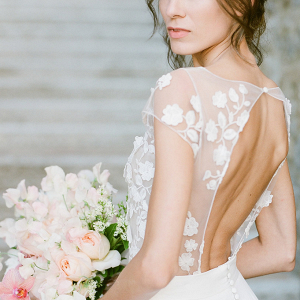 Bride with open back, floral applique gown and light pink bouquet