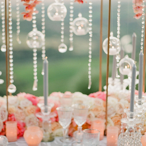 coral tablescape featuring glass orbs and hanging crystals