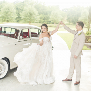 Bride and groom dancing alongside a vintage car
