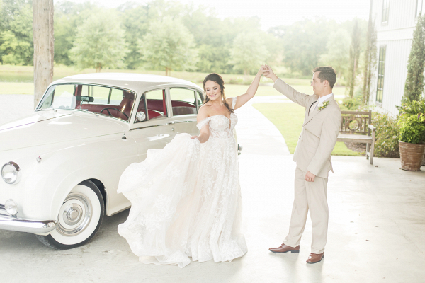 Bride and groom dancing alongside a vintage car