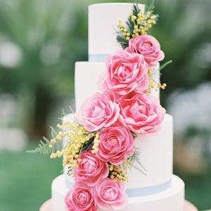 A Clean White Wedding Cake with Pink and Yellow Flowers