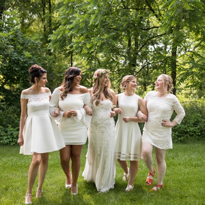 Bridesmaids in mismatched short white dresses