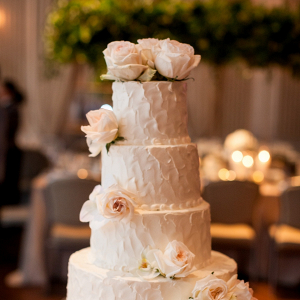 Classic white buttercream wedding cake with fresh flowers