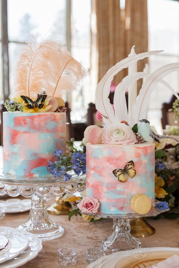 Pastel painted wedding cakes with feather toppers